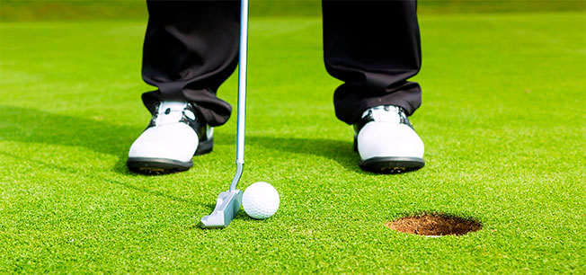 feet in position to make a putt on a golf green